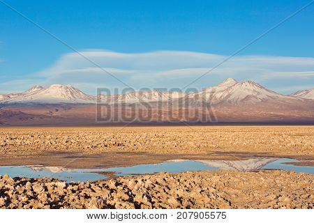beautiful landscape view of salty tebinquiche lagoon in atacama desert chile with andes mountains in the background and lenticular clouds in the sky