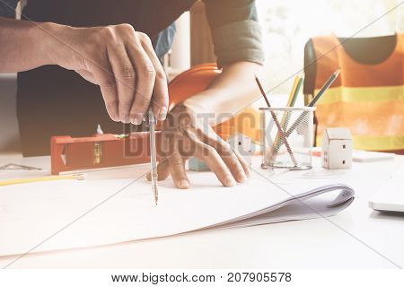 Engineer or Architect concept Image of engineer drawing a blue print design building or house An engineer workplace with blueprints pencil protractor and safety helmet Industry concept