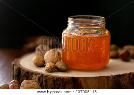 Peach jam in a transparent jar on the dark background