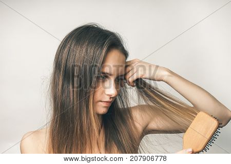 Happy woman combing hairs with comb,nice girl, long hair