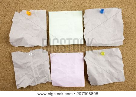 A set of office work related yellow colored paper sticky notes. Isolated n cork board background with copy text include clipping path. Businnes concept