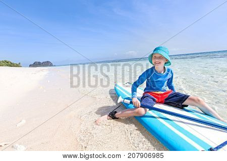 positive smiling boy enjoying stand up paddleboarding active healthy vacation concept wide angle with copy space on left