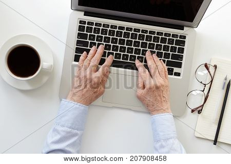 Top view of elderly woman's hands keyboarding on generic laptop computer. Senior female in formal shirt working online using notebook pc sitting at white desk with mug copybook and glasses