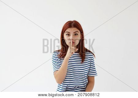 Cute young Caucasian mother holding finger at her mouth asking to keep silent because her baby sleeping in next room. Picture of attractive girl saying Shh pressing index finger against lips