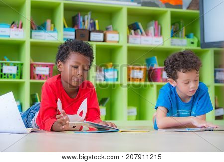 Two boy kid lay down on floor and reading tale book in preschool libraryKindergarten school education concept.
