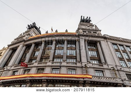 Madrid, Spain - September 30, 2017: Low angle view of Spanish classic office building decorated with spanish flag in Alcala Street in Madrid