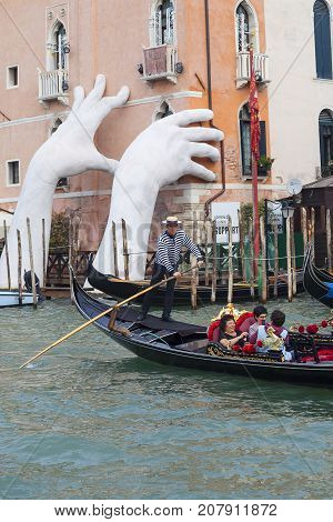 VENICE ITALY-SEPTEMBER 23 2017 : Support Sculpture putting two giant hands protruding from the Grand Canal water.Sculpture by Lorenzo Quinn draws attention to the threat of climate change