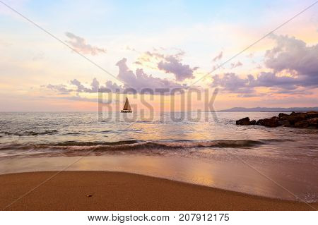 Sunset sailboat is a sailboat sailing along the ocean at sunset.