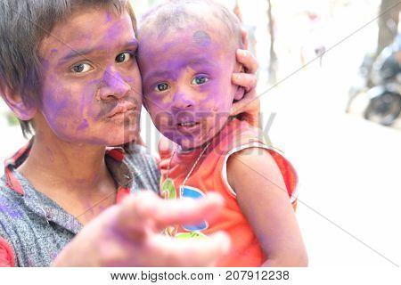 Holi celebrations - Closeup of sibling playing Holi in India