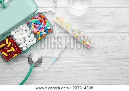 Composition with different pills, syringe and stethoscope on wooden background