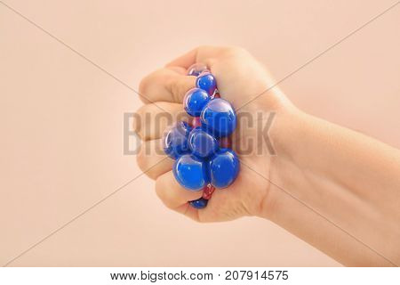 Woman's hand squeezing trendy stress ball on apricot background