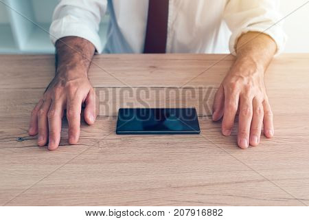Businessman fighting mobile phone addiction crisis. Business person making effort to resist using smartphone device on office desk.