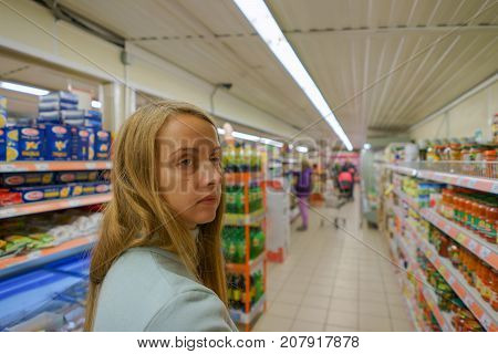 Young girl is choosing food in the market, unsure about products