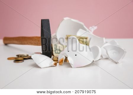 Hammer and broken piggy bank with money on white table against color background