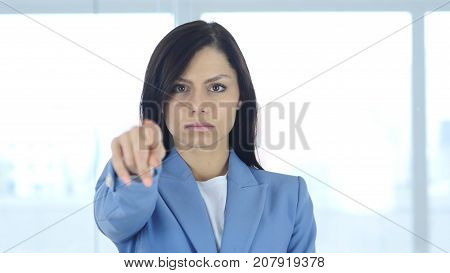 Young Businesswoman Pointing Toward Camera in Office