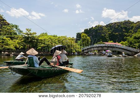 Tourists In Wooden Boats To Travel Tam Coc