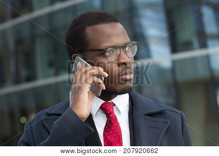 Urban Closeup Portrait Of Handsome African American Executive Standing In Street With Skyscrapers In