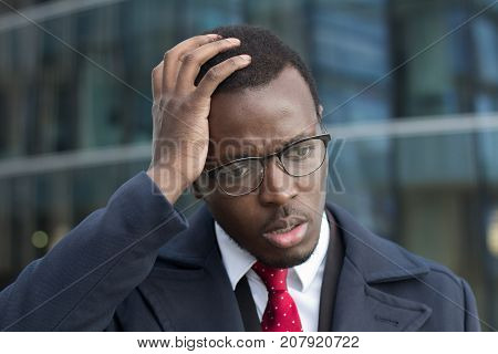 Horizontal Headshot Of Young Dark-skinned Businessman Standing Outdoors With Facepalm Gesture, Touch