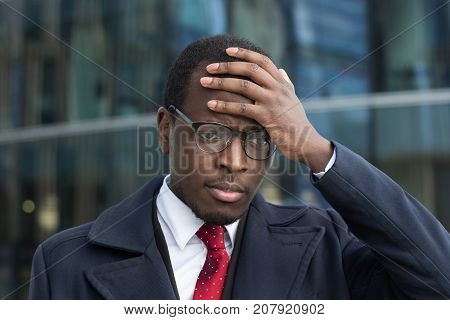 Outdoor Closeup Of Handsome African Businessman Dressed In Smart Coat, Wearing Glasses Covering Head
