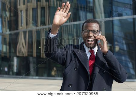 Outdoor Portrait Of Handsome African Guy In Eyeglasses, Tie And Black Coat Talking On Cellphone With