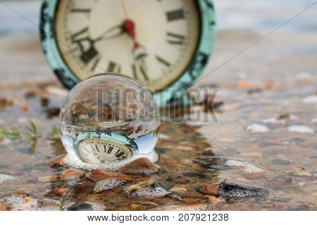 Transparent glass ball in the water on a beach reflecting an antique clock