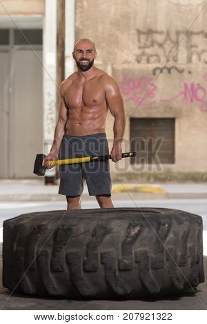 Athletic Man Hits Tire In Gym