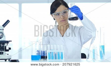 Scientist Looking At Reaction Happening In Flask In Laboratory