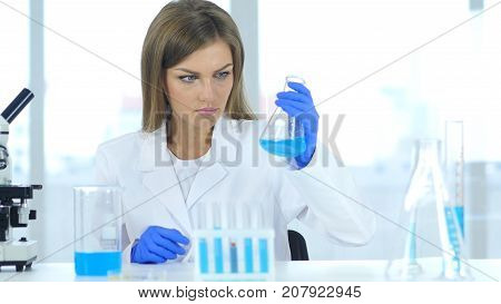 Female Scientist Looking At Reaction Happening In Flask In Laboratory