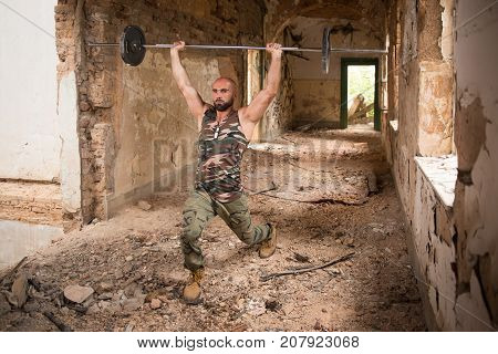 Man In Ruins Exercising Shoulder With Barbell