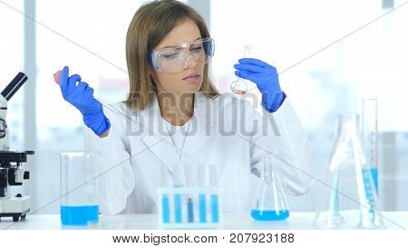Female Research Scientist Doing Chemical Reaction In Laboratory