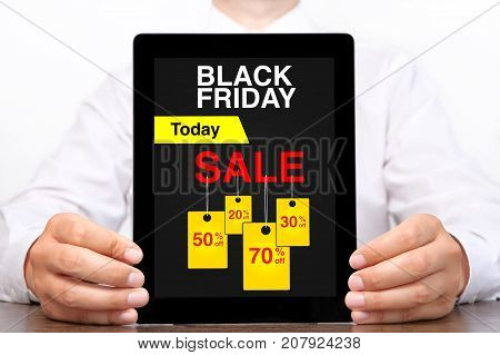 man holding tablet computer with sale black Friday on screen