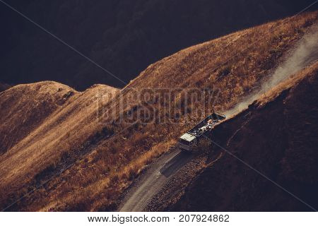 Driving car on mountain unpaved road. White lorry truck on road. Highland landscape. Transportation industry. Cargo traffic. Carriage concept. Motor-traction. Dirt mount road. Copy space. Top view.