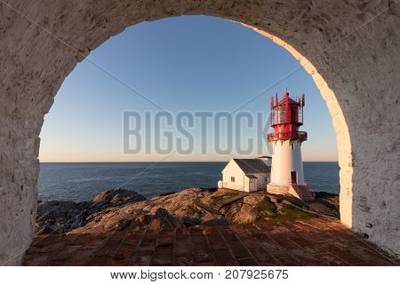 Lindesnes Fyr, historic lighthouse in Norway, seen through a rounded window in a nearby building. Red and white lighthouse on the edge of rocky sea coast in the southern most place in Norwegian mainland