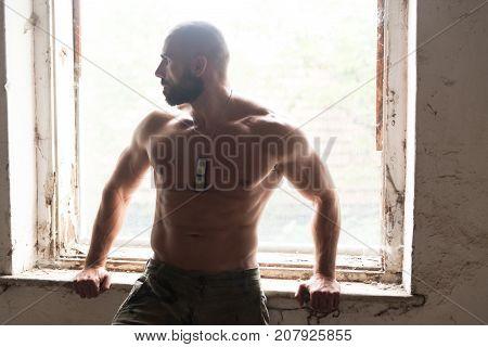 Handsome Man Flexing Muscles In Refuge