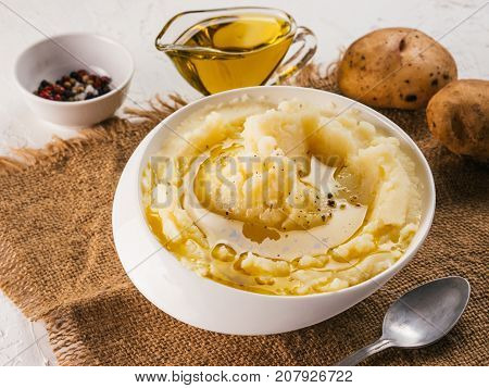 Mashed potatoes in white bowl with sackcloth, pepper and olive oil on textured concrete white background