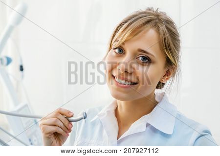 Young Professional Woman Dentist in the Office with Dental Drill