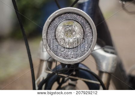 A headlight of a bicycle with drops after rain