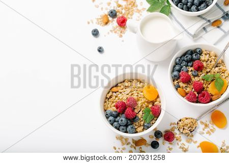 Homemade granola and healthy breakfast ingredients - milk dried fruit and berries on white background