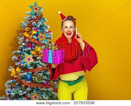 Woman With Christmas Present Box Speaking On A Smartphone