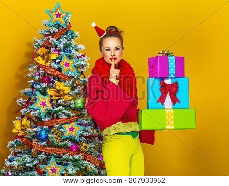 Woman With Pile Of Christmas Present Boxes Showing Shh Gesture