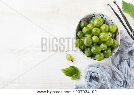 Fresh raw gooseberry berries in white ceramic plate on light wooden background. Selective focus. Rustic style.top view.