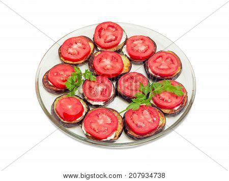 Chopped by circles roasted eggplants with garlic sauce and chopped fresh tomatoes on glass dish on a white background