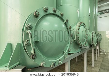 Large, massive inspection hatch in a sand filter. Industrial filtering equipment.