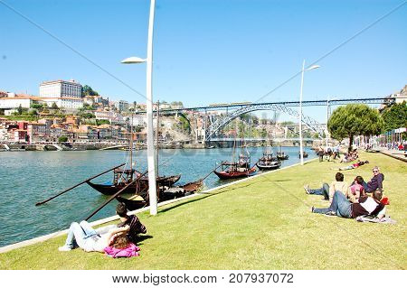 31 may 2013-oporto-portugal-young boy resting on the banks of the douro river in portugal