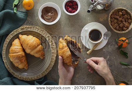Cosy winter or autum breakfast with coffee and croissants hands holding a knife spreading a chocolate butter inside a croissant view from above