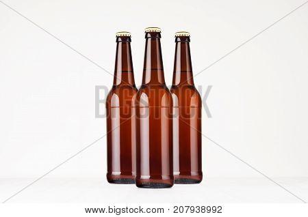 Group brown longneck beer bottles 500ml mock up. Template for advertising design branding identity on white wood table.