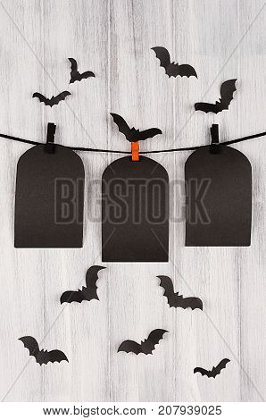 Blank black sale labels tomb hanging on clothespins with flock bats on white wooden plank background. Halloween template for advertising design cover.