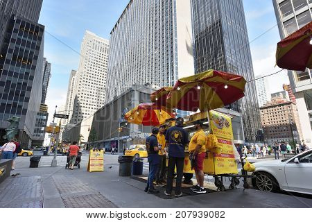 NEW YORK CITY USA - AUG. 28 : Street food cart in Manhattan on August 28 2017 in New York City NY. Manhattan is the most densely populated borough of New York City.
