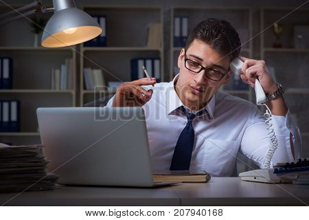 Businessman speaking on phone and smoking in office