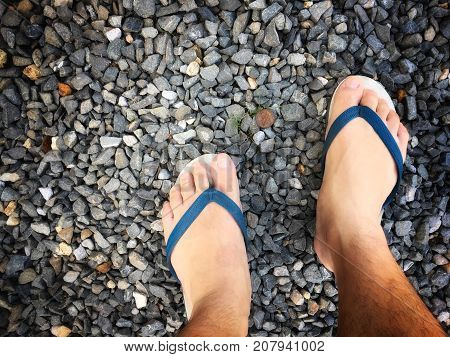 Feet Of A Man Wearing Sandals Or Flip Flops On The Old Stone Concrete Floor For Summer Time Vacation